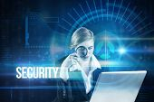 The word security and redhead businesswoman using her laptop against blue technology interface with