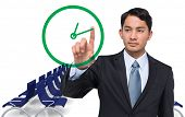 Composite image of serious asian businessman pointing to a clock