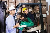 Warehouse manager talking with forklift driver in a large warehouse