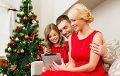 family, christmas, x-mas, technology and people concept - smiling family with tablet pc