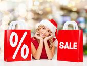 sale, gifts, christmas, holidays and people concept - smiling woman in santa helper hat with shoppin