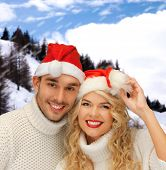 winter, holidays, christmas and people concept - smiling couple in sweaters and santa helper hats ov