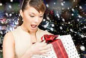 christmas, holidays, celebration and people concept - smiling woman in red dress with gift box over