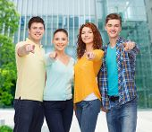 friendship, business, education and people concept - group of smiling teenagers over campus backgrou