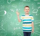 childhood, gesture, education and people concept - smiling little boy in casual clothes making OK gesture over green board with doodles background