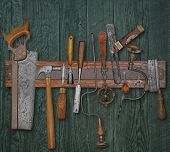 vintage woodworking tools on a magnetic rack against the wooden wall