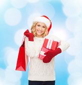 happiness, winter holidays, christmas and people concept - smiling young woman in santa helper hat w