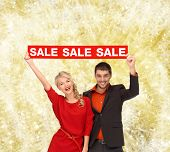 sale, shopping, christmas, holidays and people concept - smiling man and woman in red dress with red