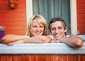 a young couple sitting in hot tub (focus is on the man) shallow DOF