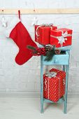 Christmas presents on blue bookcase on brick wall background