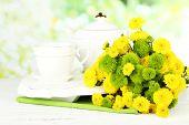 Bouquet of flowers, teapot and cup on wooden table, on bright background
