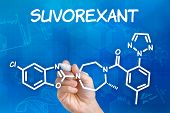 Hand with pen drawing the chemical formula of Suvorexant