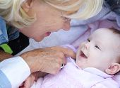 stock photo of tickle  - Close up portrait of a happy grandmother smiling with baby girl