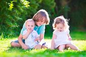 stock photo of three sisters  - Three happy kids brothers and sister laughing teenager boy little baby and a funny curly girl playing together with flowers in a sunny garden of their backyard on a warm sunny day - JPG