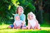picture of three sisters  - Three happy kids brothers and sister laughing teenager boy little baby and a funny curly girl playing together with flowers in a sunny garden of their backyard on a warm sunny day - JPG