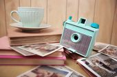 Still life with vintage camera and photos. Blur effect, focus on camera