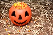 A plastic Halloween pumpkin filled with candy corn on a wood table scattered with straw.
