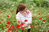 Mother And Her Newborn Baby In A Beautiful Flower Field