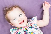 Funny Laughing Baby Girl In A Colorful Dress On A Purple Blanket