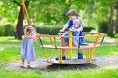 stock photo of playground school  - Three happy children laughing teenager boy cute baby and adorable toddler girl brothers and sister playing together on a playground swing enjoying a sunny hot summer day - JPG
