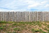 foto of log fence  - A fence made of old cracked logs on a background of blue sky - JPG