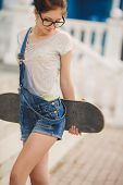 Young beautiful woman with a Board for riding on the street.