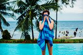 picture of infinity pool  - A young woman is drying herself with a towel by a swimming pool with palm trees and the ocean in the background - JPG