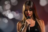 pic of singer  - A young pretty woman singer singing with eyes closed holding a microphone - JPG