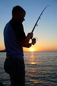 Fisherman Fishes At The  Sunset