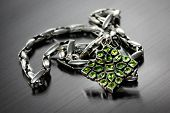 foto of lolita  - silver necklace with green stones lies on the background - JPG