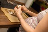 Closeup Pregnant Woman Cutting Mushrooms In The Kitchen