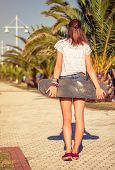 Back view of girl with a skateboard outdoors on summer