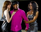 stock photo of threesome  - charming single man with two women at a nightclub - JPG