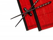 Black Chinese Chopsticks On Red Bamboo Mat. Asian Style