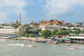 Grand Palace With Long Tail Boat In Chao Phraya River In Bangkok, Thailand
