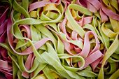 Background Of Colorful Pasta As Texture, Close-up. Mixed Colors Yellow, Pink, Green Pasta