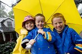 Children Playing In Rain With Yellow Umbrell