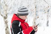 Teenager boy writes sms in winter park
