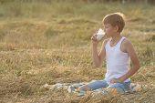 Teenage Farmer Boy With Closed Eyes Drinks Milk