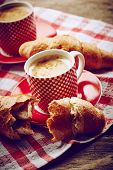 image of croissant  - Cup of coffee with croissant on wooden background - JPG