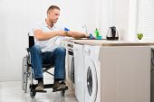 stock photo of handicapped  - Young Handicapped Man On Wheelchair Cleaning Induction Stove - JPG