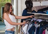foto of wardrobe  - Beautiful teenage girl looking wardrobe in a boutique - JPG