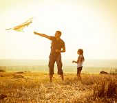 picture of kites  - Dad with his little daughter let a kite in a field - JPG