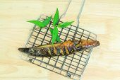 stock photo of catfish  - Grilled catfish and gridiron on wooden background - JPG