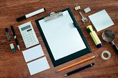 stock photo of neat  - High Angle View of Office or School Supplies Arranged Neatly Around Clipboard with Blank Page on Wooden Desk Surface - JPG