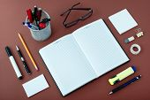 pic of neat  - High Angle View of Office or School Supplies Arranged Neatly Around Notebook Open to Blank Page on Wooden Desk Surface - JPG
