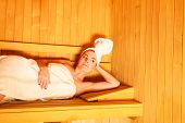 foto of sauna woman  - Spa beauty well being and resort concept. Woman white towel lying relaxed in wooden finnish sauna