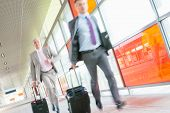image of carry-on luggage  - Middle aged businessmen with luggage rushing on railroad platform - JPG