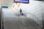 pic of upstairs  - Rear view of businesspeople with luggage moving upstairs in railroad station - JPG