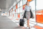 stock photo of carry-on luggage  - Full length of young businesswoman with luggage walking in railroad station - JPG